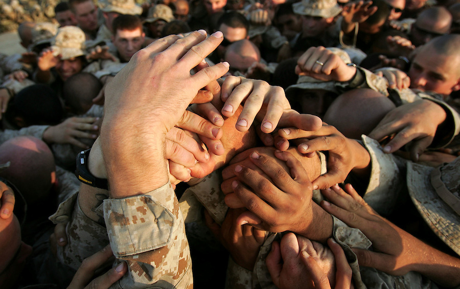 The Marines of  Kilo Co. 3rd Battalion 1st Marine Regiment (3/1) join hands in a symbolic act of unity before leaving their base for the commencement of Operation River Gate - a search for insurgents and weapons in the Al-Anbar Province city of Haditha, Iraq on Monday. Oct. 3, 2005. The operation which began in the pre-dawn hours met virtually no resistance as insurgents melted away into the city's populace.