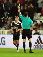 Marc Albrighton of Leicester City sees a yellow card by match referee Michael Oliver during the Barclays Premier League match between Swansea City and Leicester City at the Liberty Stadium, Swansea on December 05 2015