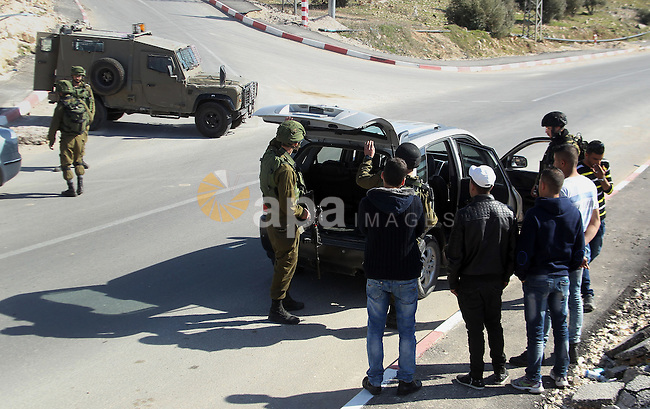 Israeli army soldiers check the cars following a demonstration against the construction of Jewish settlements in the occupied West Bank city of Hebron, on February 10, 2017. Photo by Wisam Hashlamoun