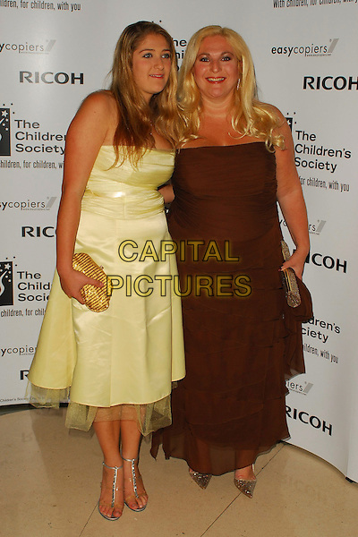 VANESSA FELTZ & DAUGHTER.The Children's Society annual ball, this year celebrating the society's 125th anniversary with a fairytale theme at Claridges Ballroom, London, UK..May 17th, 2006.Ref: CAN.full length mother family yellow brown dress strapless.www.capitalpictures.com.sales@capitalpictures.com.©Capital Pictures