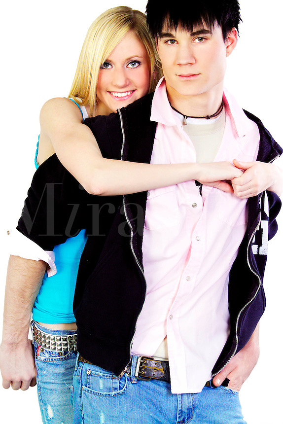 Teenage boy and girl standing with their arms around each other, in love.
