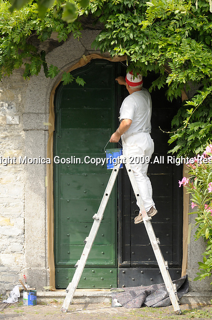 A man dressed in all white and wearing a red and white striped cap, stands on a ladder and paints a door green in Menaggio on Lake Como, Italy.  .