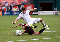 Kelyn Rowe (11) of the New England Revolution has the ball tackled away from him by John Thorrington (8) of D.C. United during a Major League Soccer game at RFK Stadium in Washington, DC.  New England defeated D.C. United, 2-1.