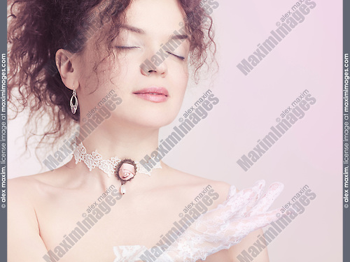 Closeup face portrait of young beautiful woman wearing a lace choker with pink rose and white lacy gloves on pink background