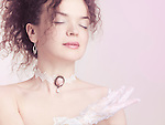Closeup face portrait of young beautiful woman wearing a lace choker with pink rose and white lacy gloves on pink background Image © MaximImages, License at https://www.maximimages.com