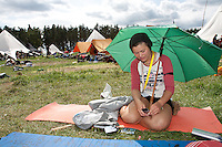 Umbrella also used for shade. Oda is a scout from Norway, last day at camp. Photo: Anders Forsell