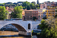Fine Art Landscape Travel Print Photograph. A romantic river scene photographed in the ancient city of Rome. The lighting of the day reveals the subtle textures of the bridge, and the Colourful building that gracefully line the banks of the river shoreline.