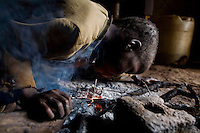 Seven year old Samson warms himself over some ashes. He is an orphan looked after by his grandfather Rabson. Both Samson and his grandfather are HIV positive.