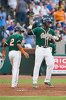 K.J. Woods (32) of the Greensboro Grasshoppers highs fives teammate Rony Cabrera (2) after hitting a home run against the Greenville Drive at NewBridge Bank Park on August 17, 2015 in Greensboro, North Carolina.  The Drive defeated the Grasshoppers 5-4 in 13 innings.  (Brian Westerholt/Four Seam Images)