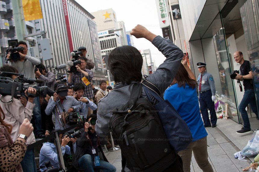 A customer celebrates as he is let into the Apple store at the  official release of the iphone4S in Ginza, Tokyo, Japan. Friday October 14th 2011. The latest version of the popular iphone was released worldwide on October 14th. Japans flagship Apple store in Ginza was opened at 8am for the 800 people that had been waiting to be the first to purchase the new telephone.