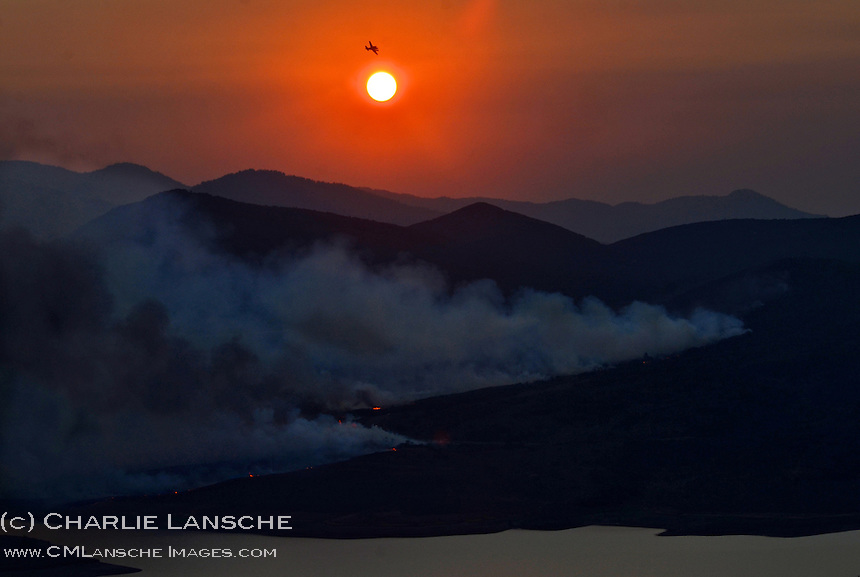 A tanker pilot soars above the Fox Den Fire near Park City, Utah following a series of  late evening strafing missions.  August 2012.