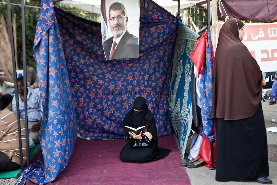 Une femme lit le Coran au sit-in pro morsi de L'universit&eacute; du Caire. <br /> <br /> A woman is reading the Coran during a pro Morsi sit-in at the University of Cairo.