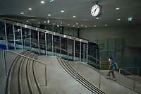 Switzerland. Canton Ticino. Lugano. Lugano railway station is also the terminus of the Lugano Città–Stazione funicular. The funicular provides a direct link from the station to the city centre below. A woman is walking the stairs. She wears a mask on her face to protect herself from the Coronavirus (also called Covid-19). The safety sanitary measures advocate people to stand apart in order to avoid close contact and potential contamination by coronavirus. A clock is fixed on the ceiling.17.07.2020 © 2020 Didier Ruef