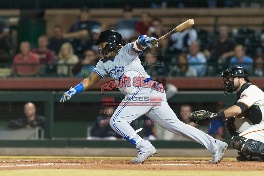 Surprise Saguaros third baseman Vladimir Guerrero Jr. (27), of the Toronto Blue Jays organization, follows through on his swing in front of catcher Matt Winn (16) during an Arizona Fall League game against the Scottsdale Scorpions at Scottsdale Stadium on October 15, 2018 in Scottsdale, Arizona. Surprise defeated Scottsdale 2-0. (Zachary Lucy/Four Seam Images)