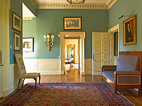 The hallway has been painted an historical green and is furnished with a 20th century sofa