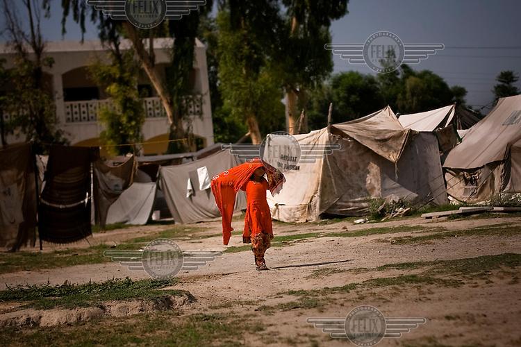 A girl dressed in red walks through a tented camp set up for people made homelss by the severe floods that hit in summer 2011.