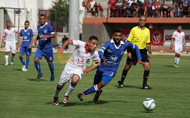 Palestinian players of Shabab Khan Younis football club (white) compete with Palestinian players of Shabab Rafah football club (blue) during the final football match of the Palestine Cup for the southern governorates at Palestine stadium in Gaza city on April 30, 2018. Photo by Mahmoud Ajour