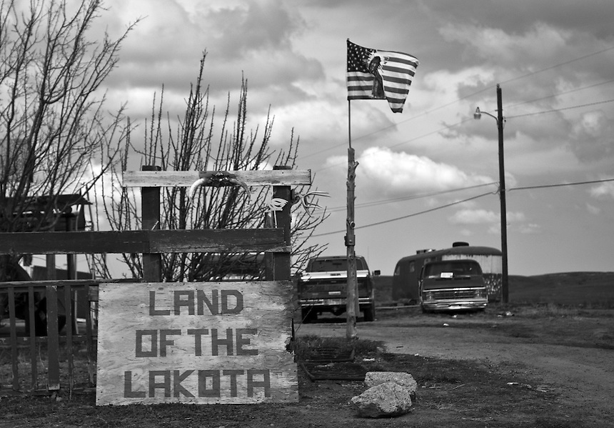 A typical Pine Ridge Reservation landscape with abandoned cars and and handmade sign Land of the Lakota in front of one of the houses in the Reservation.The Pine Ridge Indian Reservation in South Dakota, U.S. is unlike any other place in the world.  Here the past and the present merge like two powerful rivers meeting, generating raging rapids and deep undercurrents.  A people living in dire poverty under conditions equivalent to occupation have embraced the past, embraced once lost traditions, in order to struggle against the oppression of their present lives.