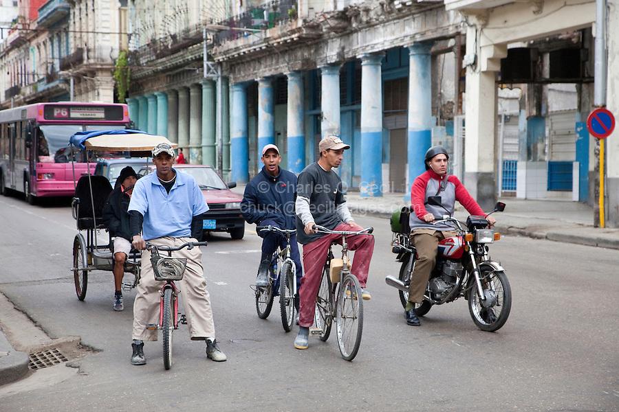 Cuba, Havana.  Early Morning Central Havana Street Scene.  Bicyclists.