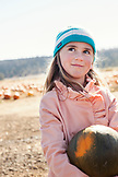 USA, Oregon, Bend, a young girl finds a pumpkin to take home at the annual pumpkin patch located in Terrebone nearcSmith Rock State Park