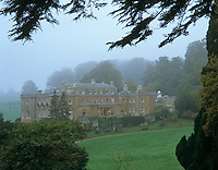 The exterior of Daylesford seen through the trees on a foggy afternoon