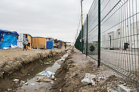 """Separation between the """"old camp"""" (on the left) and the containers' """"new camp"""" protected by high fences, security guards and finger prints reader at the gate used as the """"key"""" to enter.<br /> <br /> Calais Jungle Camp.<br /> <br /> Under the Sky of Calais & Dunkirk. Two Camps, Two Sides of the Same Coin: Not 'migrants', Not 'refugees', just Humans.<br /> <br /> France, 24-30/03/2016. Documenting (and following) Zekra and her experience in the two French camps at the gate of the United Kingdom: Calais' """"Jungle"""" and Dunkirk's """"Grande-Synthe"""". Zekra lives in London but she is originally from Basra in Iraq. Zekra and her family had to flee Kuwait - where they moved for working reason - due to the """"Gulf War"""", and to the Western Countries' will to """"export Democracy in Iraq"""". Zekra is a self-motivated volunteer and founder of """"Happy Ravers"""", a group of people (not a NGO or a charity) linked to each other because of their love for rave parties but also men and women who meet up every week to help homeless people and other people in need in Central London. (Here there are some of the stories I covered about Zekra and """"Happy Ravers"""": http://bit.ly/1XVj1Cg & http://bit.ly/24kcGQz & http://bit.ly/1TY0dPO). Zekra worked as an English teacher in the adult school at Dunkirk's """"Grande-Synthe"""" camp and as a cultural mediator and Arabic translator for two medic teams in Calais' """"Jungle"""". Please read her story at the beginning of this reportage."""