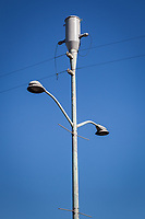 A simple utility pole, with imagination, reveals arms ending in street lamp hands, a mouth or maybe two, and a head with extended ears.