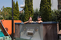 Romania - Timisoara - Nathali Rose (left) and Domina Monserrat (right) relax in the jacuzzi in the courtyard of the Live Cams Mansion before going to work in their rooms.