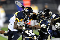 26 September 2009:  Toledo running back DaJuane Collins (22) attempts to break away from FIU cornerback O'Darris D'Haiti (20) in the  .second quarter of the Toledo 41-31 victory over FIU at FIU Stadium in Miami, Florida.