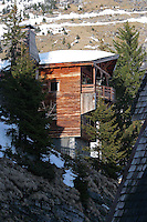 Side view of the wooden-clad chalet with its roof covered with snow and the mountainside rising behind it