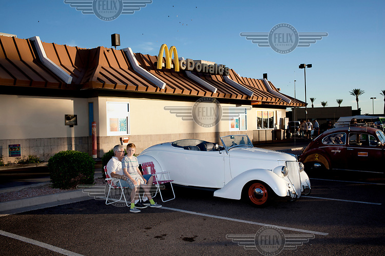 A man and young boy sitting beside their vintage car, on display outside a McDonald's restaurant during a weekly car show where the owners of various cars come to show them off.