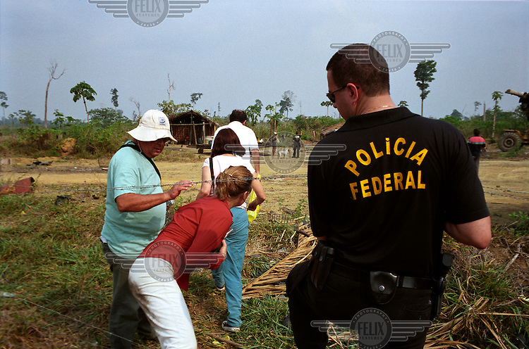 A Federal Police officer helps the Ministry of Labour's inspectors cross a barbed-wire fence during a grupo movel (mobile unit) operation where they raided a charcoal producing farm. Due to widespread unemployment and poverty, many workers risk their lives and freedom to take work in neighbouring states on farms that use unfree labour. This form of modern-day slavery is implicated most often via a fraudulent debt, used as an excuse to keep workers in the farm while they owe money to the farmer. They are forced to buy everything, from tools to food, from the farmer's shop, at inflated prices. The debt is never cleared and the workers are effectively trapped. The Federal Police and Ministry of Labour work to try and break this cycle of exploitation by raiding farms whenever they receive a tip-off that workers are being mistreated.
