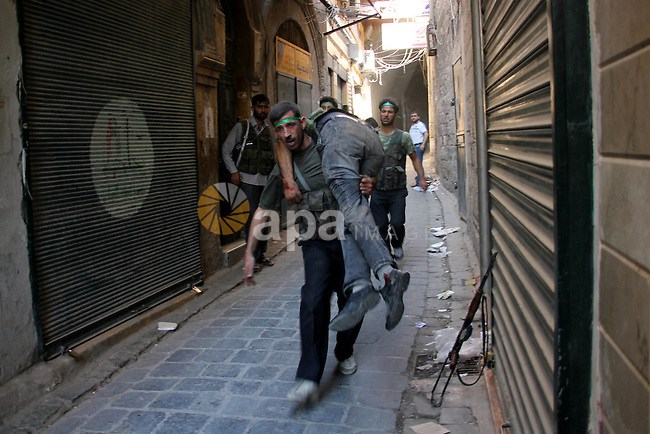 A Free Syrian fighter is brought to the Dar al-Shifa hospital in the northern city of Aleppo to be treated for his wounds on September 27, 2012, as fighting in Syria's second largest city between rebel forces and government troops continues. Photo by Ahmed Deeb