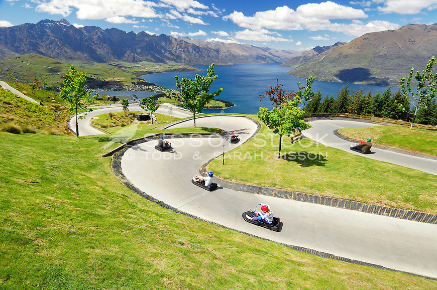 Tourists on the luge track up the Skyline Gondola with view of Lake Wakatipu and the Remarkables, Central Otago, South Island, New Zealand