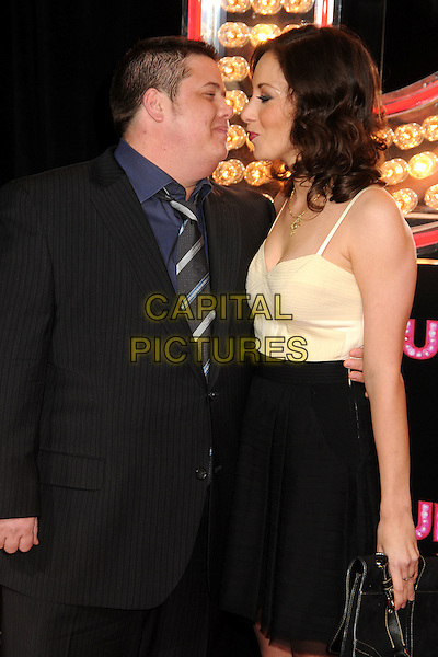 "CHAZ BONO & JENNIFER ELIA .""Burlesque"" Los Angeles Premiere held at Grauman's Chinese Theatre, Hollywood, California, USA, .15th November 2010..Chastity half length couple suit cream bustier top dress black black tie navy blue shirt arm around kissing kiss profile .CAP/ADM/BP.©Byron Purvis/AdMedia/Capital Pictures."