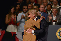 MIAMI, FL - JUNE 16: US President Donald Trump hugs Cuban dissidents Cary Roque as he speaks at the Manuel Artime Theater in Miami, Florida on June 16, 2017. Trump on Friday vowed to roll back his predecessor Barack Obama's deal re-opening trade ties with Havana, in favor of measures to support the Cuban people against what he called their 'cruel and brutal' regime.  Credit: MPI10 / MediaPunch