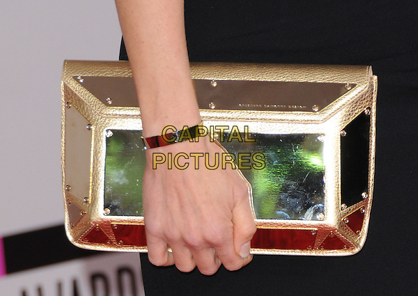 JULIE BENZ'S CLUTCH BAG .At The 2010 American Music  Awards held at Nokia Theatre L.A. Live in Los Angeles, California, USA,.November 21st 2010..amas arrivals detail hand metallic shiny hand bracelet .CAP/RKE/DVS.©DVS/RockinExposures/Capital Pictures.