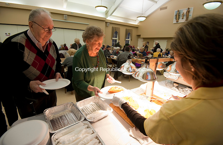 SOUTHBURY, CT--- -030416JS01- Ray and Mary Vogel of Southbury, gets their fish dinner served to them by Rosanne Verlezza, right, during the annual fish fry held Friday at Sacred Heart Church in Southbury. The event was hosted by the Southbury Knights of Columbus and Columbiettes. Proceeds from the event with benefit the Knights of Columbus Council 5066 scholarship and supported charities.   Jim Shannon Republican-American