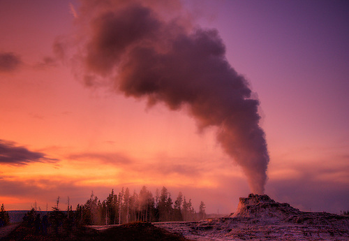 CASTLE GEYSER ERUPTS DURING SUNSET AT YELLOWSTONE NATIONAL PARK,WYOMING
