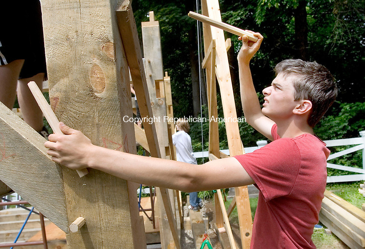 FARMINGTON CT. 06 June 2015-060615SV13-Steve Hintz, 17, of Torrington puts a wooden dowel in a hole to hold a beam of a heavy timber barn the class was building in Farmington Saturday. Students in a construction technology class of Torrington High were building the barn as their final exam. <br /> Steven Valenti Republican-American