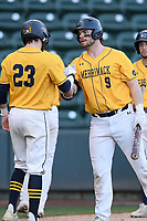 Third baseman Joey Porricelli (23) of the Merrimack Warriors is greeted by Thomas Joyce (9) after scoring a run in a game against the Michigan State Spartans on Saturday, February 22, 2020, at Fluor Field at the West End in Greenville, South Carolina. Merrimack won, 7-5. (Tom Priddy/Four Seam Images)