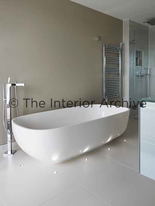 The elegant, free-standing bath is surrounded by discreet lights embedded in the tiled floor.