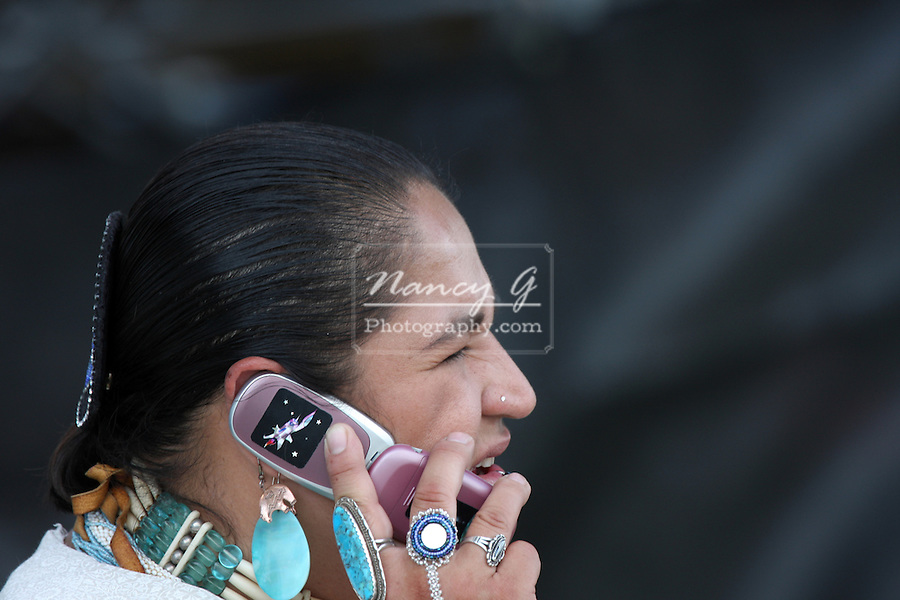 A female Native American Indian dancer talking on a cell phone at a Pow Wow at the Milwaukee Lakefront Indian Summer Festival, Wisconsin