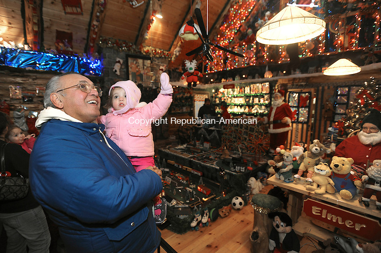 TORRINGTON, CT 11 DECEMBER- 121112JS02-Joe Frascatore of Waterbury and his one-year-old granddaughter Adrianna Colwell of Southington, look over all the toys on display inside the Toy Shop during their first visit to Christmas Village in Torrington on Tuesday. .Jim Shannon Republican American
