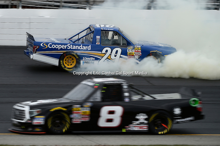 September 19, 2014 - Loudon, New Hampshire, U.S. -  Ryan Blaney, NASCAR Camping World Truck Series driver of the #29 Cooper Standard Ford truck spins out as John Hunter Nemechek #8 passes by during the NASCAR Camping World Truck Series UNOH 175 race held at the New Hampshire Motor Speedway in Loudon, New Hampshire.   Eric Canha/CSM