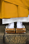 A Buddhist monk prays at a shrine in Koyasan, Japan. I zoomed in to show the beautiful contrast of mustard and white, while presenting the texture of the shrine's cracked wood. The monk's wooden slippers complete this vignette.