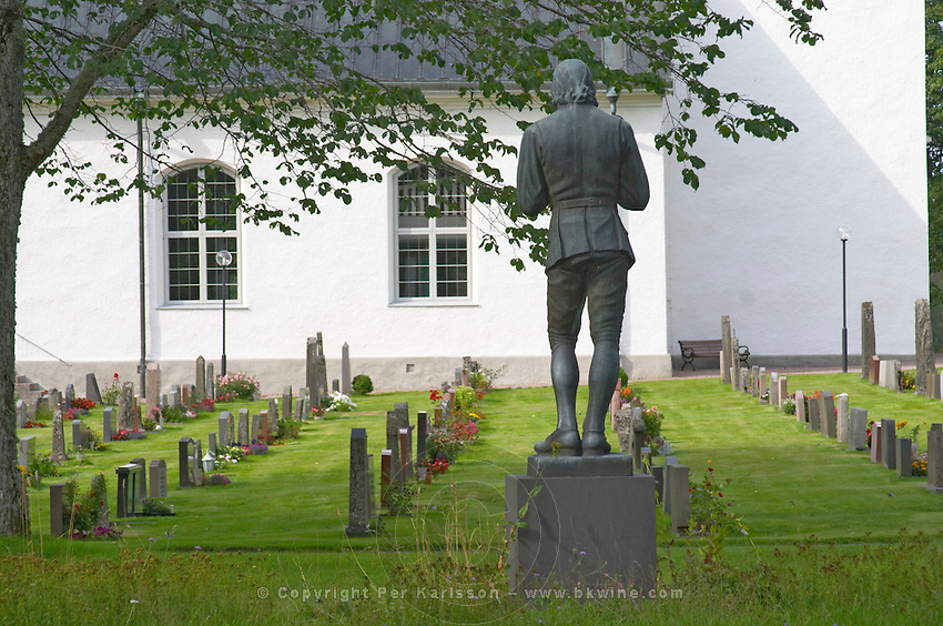 A statue of Carl Linnaeus holding a bird by Gerda Sprinchorn standing in the church yard of Stenbrohult with Linneaus' father was priest. Smaland region. Sweden, Europe.