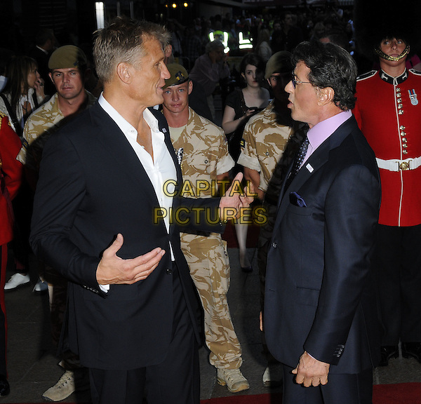 "DOLPH LUNDGREN & SYLVESTER STALLONE .Attending the UK Film Premiere of ""The Expendables"" at Odeon Leicester Square, London, England, UK. .August 9th 2010 .half length black suit white shirt jacket hands side profile pink shirt tie sly .CAP/CAN.©Can Nguyen/Capital Pictures."