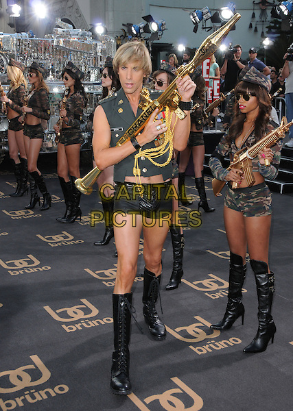 "SACHA BARON COHEN.The Universal Pictures' L.A. Premiere of ""Bruno"" held at the Grauman's Chinese Theatre in Hollywood, California, USA. .June 25th, 2009.full length army green uniform military gold chanel bazooka rocket launcher gun boots posing .CAP/DVS.©Debbie VanStory/Capital Pictures."