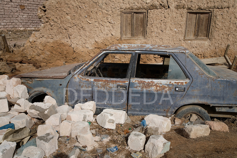 An abandoned old and rusted car stuck in the desert sand in the Siwa Oasis, Egypt.